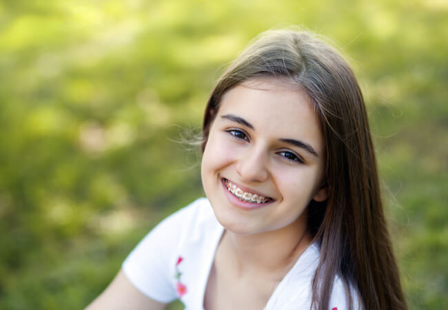 Brunette teen girl with braces smiles with healthy teeth that she keeps clean