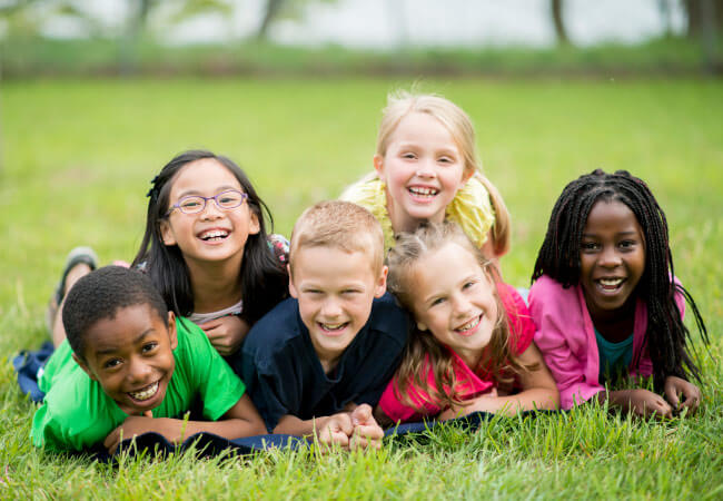 Group of multiracial children smile while lying on the green grass by Tots to Teens Pediatric Dentistry in Laredo, TX