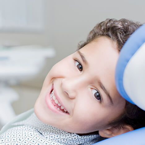 smiling young boy sitting in a dental chair