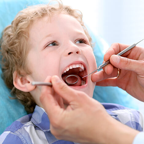 young boy having his teeth examined by a dentist