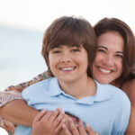 Brunette mom smiles with her son in a blue polo after he gets his braces on