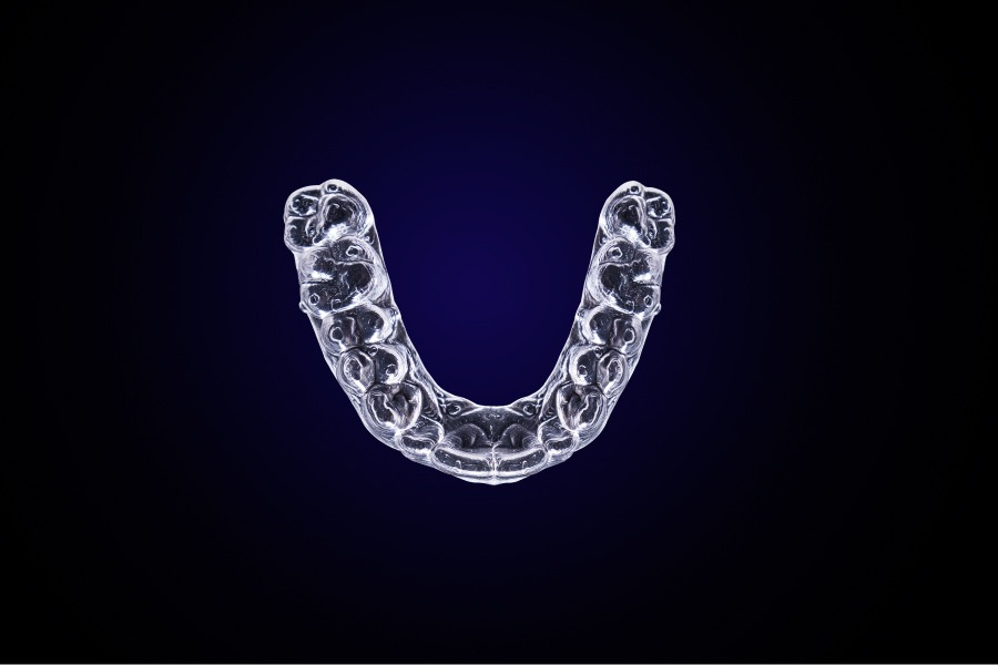 Aerial view of an Invisalign tray that can fix small gaps against a blue background