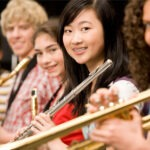 High school girl with braces smiles while holding her wind instrument in the orchestra