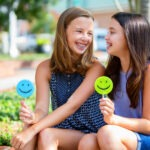 2 girls with braces smile while holding smiley faces outside on a curb