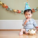 Asian baby celebrating his or her first birthday with a party hat, cake and paper chain.