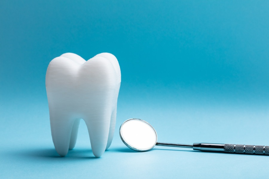 A tooth next to a dental mirror against a blue background after being extracted before braces