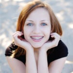 Red head teenager smiles with her braces that she keeps clean