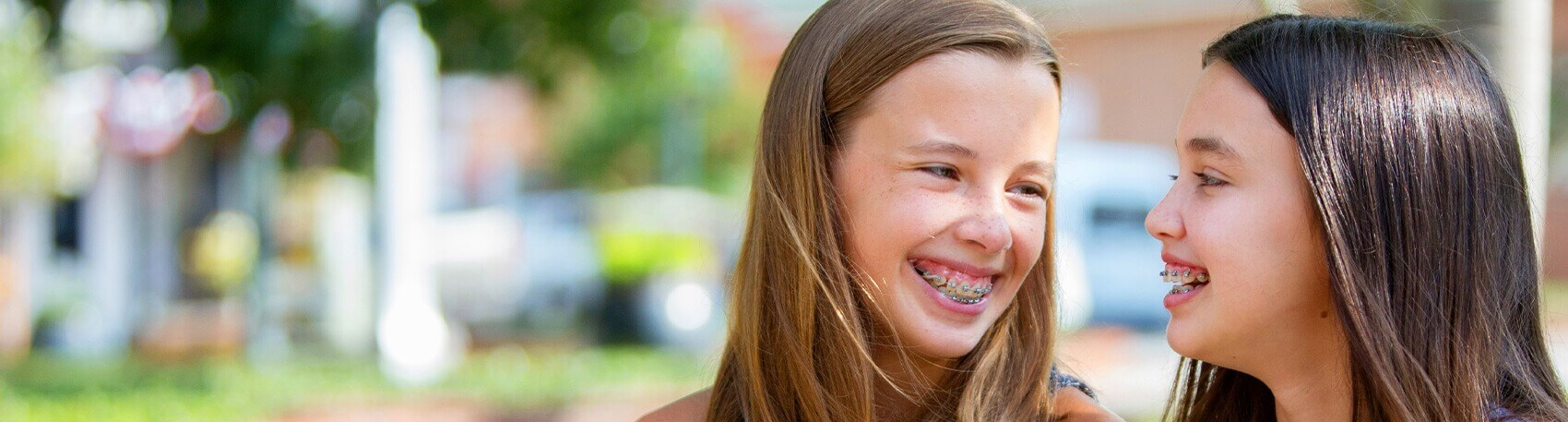 two smiling girls with braces